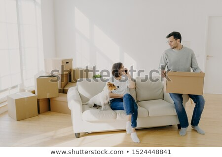 Photo of happy couple move in new home, pose on sofa with pet and boxes, have relocation, unpack box Stock photo © vkstudio