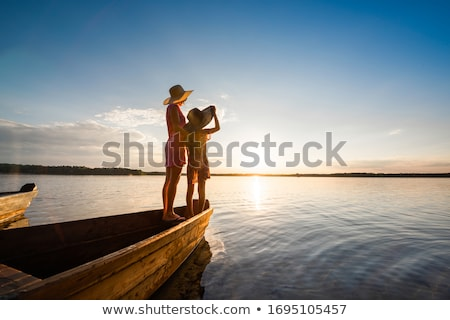 Child outdoors stands near a wooden boat at the lake Stock photo © ElenaBatkova