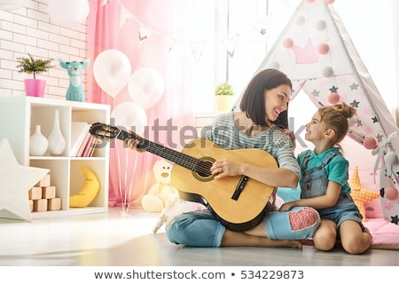 little girl playing guitar in kids tent at home Stock photo © dolgachov