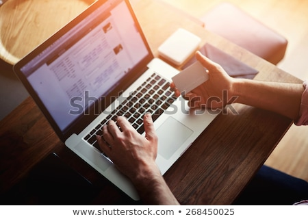 Businessman Sitting at Computer With Credit Card stock photo © Edbockstock