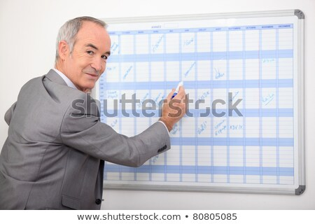 Mature businessman writing on a wall planner Stock photo © photography33