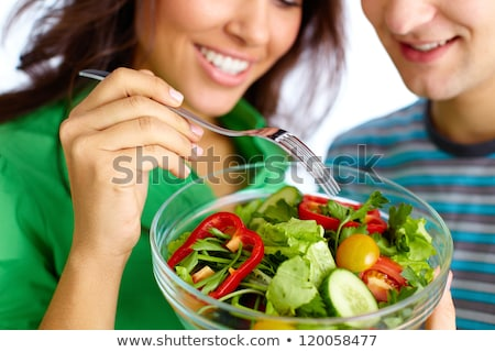 Young man eating vegetarian salad with appetite Stock photo © HASLOO