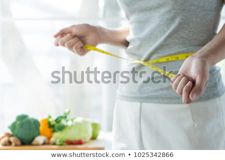 Lady is checking her weight on a scale stock photo © kittasgraphics