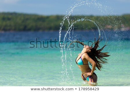 woman flicking her long hair at the seaside stock photo © smithore