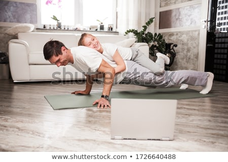 Portrait of a sporty young man doing push ups in the living room at home Stock photo © deandrobot