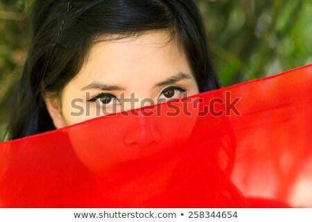 Asian woman peeking over red fabric Stock photo © smithore
