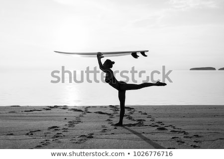 Beautiful surfer girl standing on the beach with her surfboard Stock photo © wavebreak_media