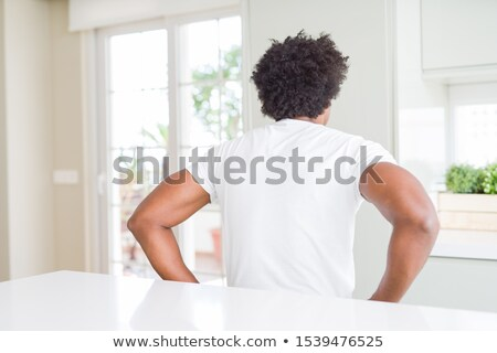 Handsome curly man in black shirt with hand behind head Stock photo © deandrobot
