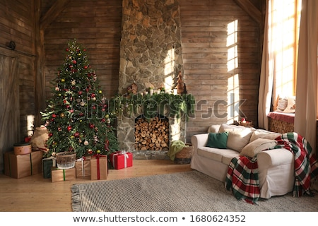 Decorated living room at home for Christmas with colorful stockings on the mantelpiece, heap of gift wrapped presents and Xmas tree, copy space on lace curtains
