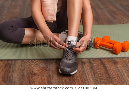 cheerful attractive young fitness woman sitting on yoga mat stock photo © deandrobot