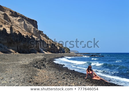 beautiful young woman sitting on big stone on the beach in Greec Stock photo © Massonforstock