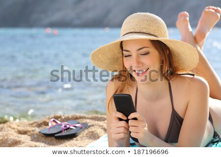 Female tourist using mobile phone at seaside on summer holiday Stock photo © stevanovicigor