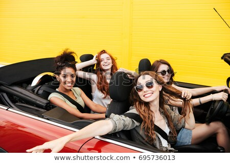 Happy emotional four young women friends sitting in car Stock photo © deandrobot