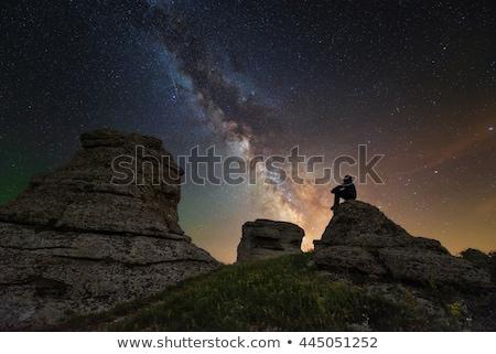 Man sitting on rocks looking at peaks Stock photo © IS2