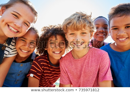 group of friends in a field smiling stock photo © is2