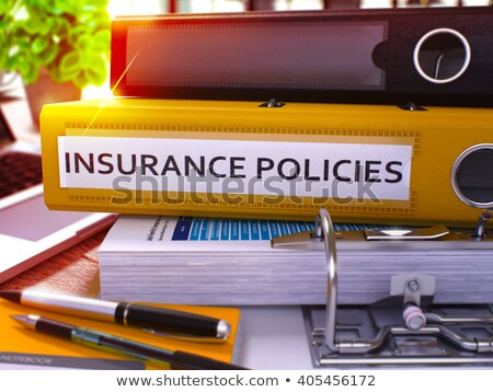 insurance policies on yellow ring binder blurred toned image stock photo © tashatuvango