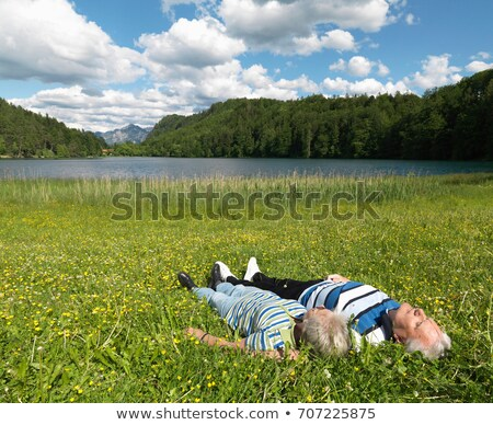 Senior couple lying in field by lake Stock photo © IS2