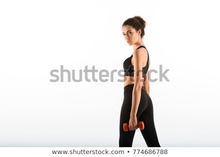 side view of calm curly brunette fitness woman holding dumbbells stock photo © deandrobot