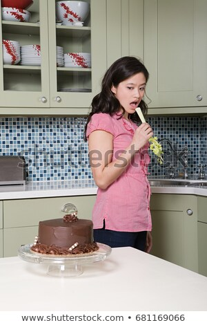 Young woman eating celery, watching chocolate cake Stock photo © IS2