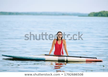 Smiling young woman kayaking on sea. Happy young woman canoeing in sea on a summer day stock photo © galitskaya