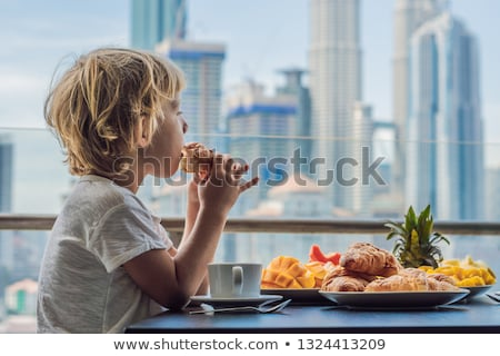 The boy is having breakfast on the balcony. Breakfast table with coffee fruit and bread croisant on  Stok fotoğraf © galitskaya