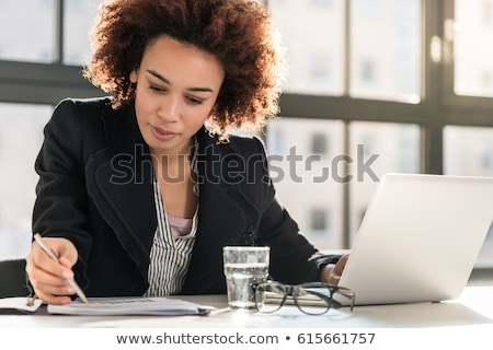 Serious young economist in eyeglasses analyzing financial papers Stock photo © pressmaster