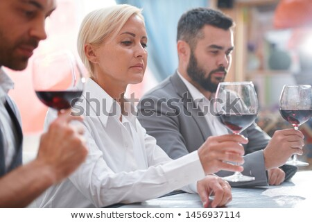 Serious blonde woman evaluating color of red wine in bokal by workplace Stock photo © pressmaster