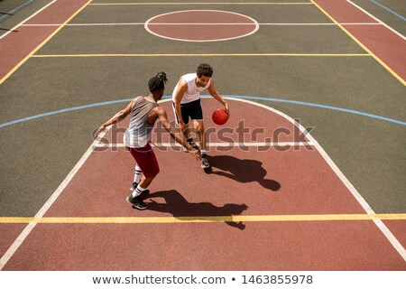 Young basketball player trying to defend ball from rival while carrying it Stock photo © pressmaster