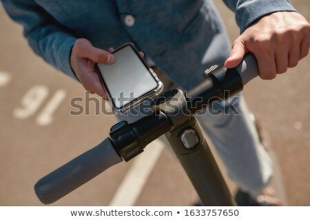 Man Using Cell Phone On Electric Scooter Stock photo © AndreyPopov