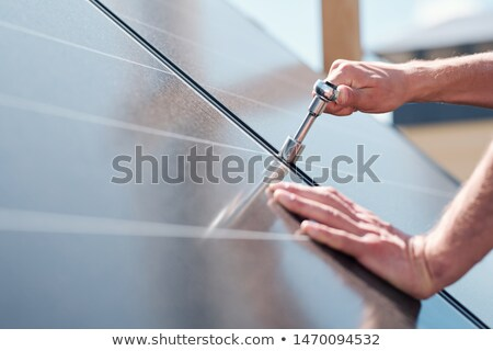 Hands of contemporary master with screw adjusting or installing solar panels Stock photo © pressmaster