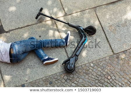Foto d'archivio: Unconscious Man Lying On Street After Accident Electric Scooter