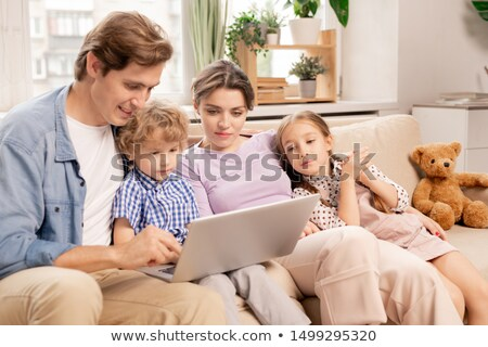 Young relaxed family in casualwear watching movie on laptop display at home Stock photo © pressmaster