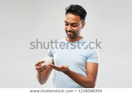 happy indian man applying lotion to his hand Stock photo © dolgachov