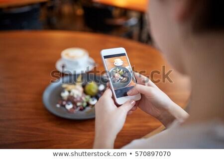 Fiatal nő okostelefon elvesz fotó cappucchino desszert Stock fotó © pressmaster