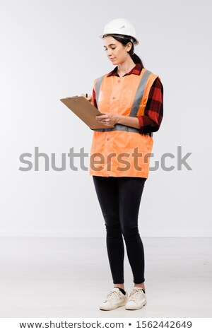 Pretty female builder in hardhat, flannel, leggins and working vest making notes Stock photo © pressmaster