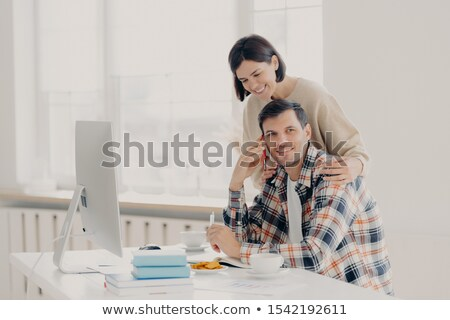 Caring woman helps her husband entrepreneur who has telephone conversation, tries to soleve working  Stock photo © vkstudio