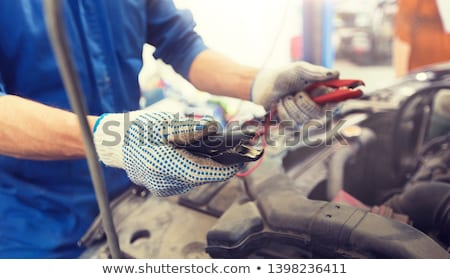 auto mechanic man with cleats charging battery Stock photo © dolgachov