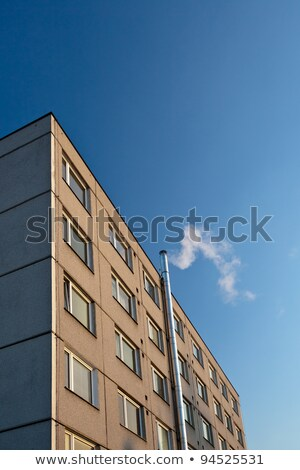 smoke/flue gases going out of a chimney by an apartment building Stock photo © lightpoet