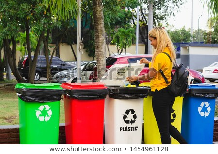 Woman placing plastic bottle into green bin Stock photo © photography33