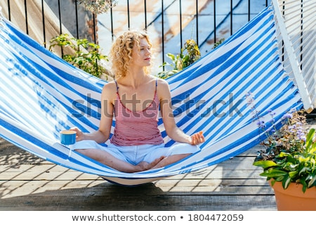blonde woman resting and drinking in a hammock stock photo © photography33