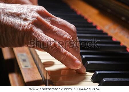 Old Hand on Piano Keys Stock photo © Gordo25