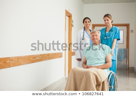 Stock photo: Patient sitting on a wheelchair next to a doctor in hospital hallway