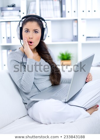 Close-up of young woman listening music through headphones stock photo © wavebreak_media