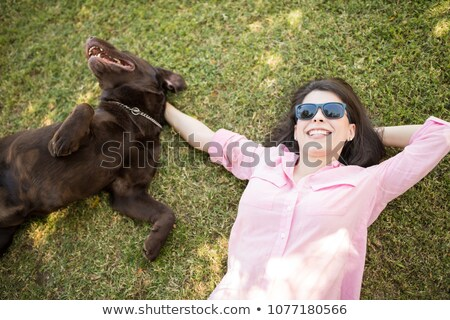 Young cheerful latin woman lying on the grass in park Stock photo © deandrobot