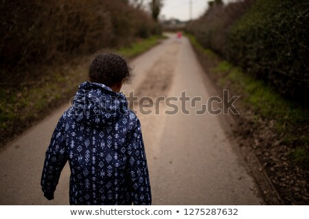 Young woman walks up a country lane alone Stock photo © sarahdoow