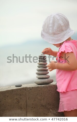 Little girl wearing pink dress and white panama hat is building a construction from pebble stones. Stock photo © Paha_L