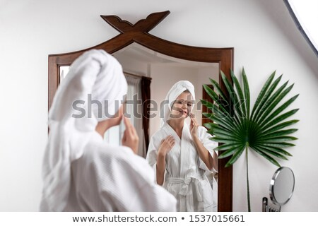 Woman with wadding looking at her reflection in mirror Stock photo © deandrobot