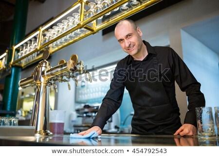 Bar tender cleaning bar counter in restaurant Stock photo © wavebreak_media