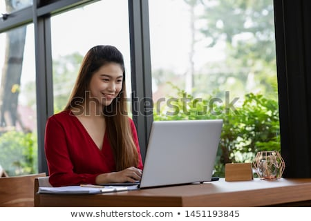 Thinking happy young business woman sitting at desk planning  Stock photo © ichiosea