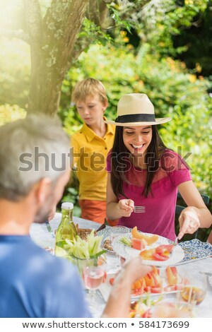 Family sitting having lunch in garden Stock photo © IS2